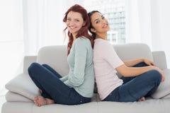 Amis féminins de sourire s'asseyant de nouveau au dos à la maison Photo stock