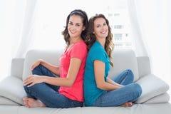 Amis féminins de sourire s'asseyant de nouveau au dos dans le salon Images stock
