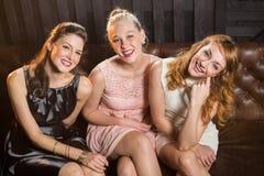 Amis féminins de sourire s'asseyant ensemble dans le sofa à la barre Image stock