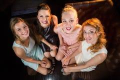 Amis féminins de sourire s'asseyant ensemble dans le sofa à la barre Images stock