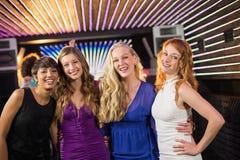 Amis féminins de sourire se tenant ensemble dans la barre Image libre de droits