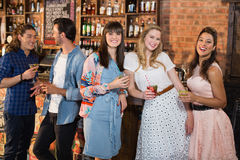 Amis féminins de sourire tenant des boissons Photo libre de droits