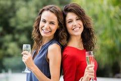 Amis féminins de sourire tenant des cannelures de champagne Image stock
