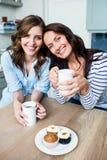 Amis féminins de sourire tenant des tasses de café à la table Photo libre de droits