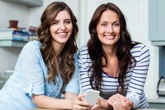Amis féminins de sourire tenant le téléphone portable Photographie stock libre de droits