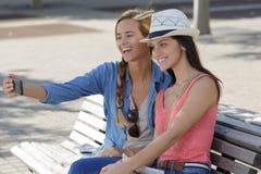 Amis féminins de touristes gais prenant les photos elles-mêmes Images stock