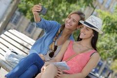 Amis féminins de touristes gais prenant les photos elles-mêmes Photos stock