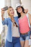 Amis féminins de touristes gais prenant les photos elles-mêmes Images libres de droits