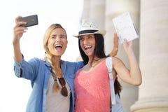 Amis féminins de touristes gais prenant les photos elles-mêmes Photo stock