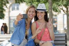 Amis féminins de touristes gais prenant les photos elles-mêmes Image stock