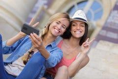 Amis féminins de touristes gais prenant les photos elles-mêmes Photographie stock