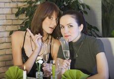 Amis féminins discutant par le dîner Image stock