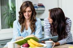 Amis féminins discutant tout en tenant le livre et le comprimé numérique Image stock