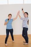 Amis féminins donnant la haute cinq dans une nouvelle maison Photo libre de droits