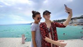 Amis féminins drôles des vacances prenant des selfies sur la plage Photos stock