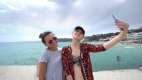 Amis féminins drôles des vacances prenant des selfies sur la plage Images stock