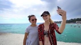 Amis féminins drôles des vacances prenant des selfies sur le pilier avec un téléphone intelligent Images stock