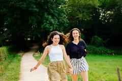 Amis féminins drôles courant dans la campagne Photo stock