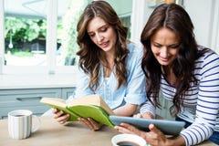 Amis féminins employant le comprimé numérique et le livre de lecture Photographie stock