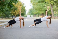 Amis féminins en bonne santé s'étirant sur un fond de parc Forme physique exerçant le concept Copiez l'espace Image stock