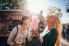 Amis féminins en parc d'attractions mangeant la sucrerie de coton Images stock