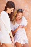 Amis féminins en vacances ensemble utilisant le téléphone portable Photos libres de droits
