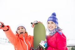 Amis féminins enthousiastes avec le surf des neiges dehors Photographie stock