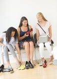 Amis féminins essayant sur de nouvelles chaussures à la maison Photos libres de droits