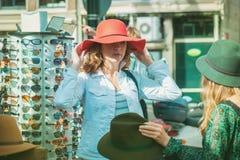 Amis féminins essayant sur des chapeaux Image stock