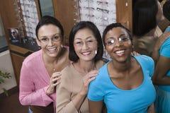 Amis féminins essayant sur des verres à l'optométriste Photo stock