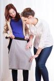 Amis féminins essayant sur la jupe de crayon Photographie stock