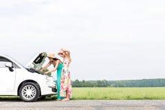 Amis féminins examinant la voiture décomposée sur la route de campagne contre le ciel clair Photo stock