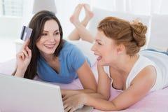 Amis féminins faisant des achats en ligne dans le lit Image stock
