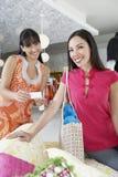 Amis féminins faisant des emplettes dans le magasin d'habillement Image stock
