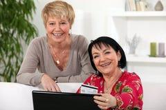 Amis féminins faisant des emplettes en ligne. Photographie stock