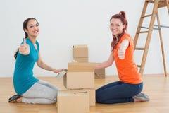 Amis féminins faisant des gestes des pouces avec des boîtes dans une nouvelle maison Photographie stock