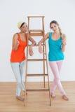Amis féminins faisant des gestes des pouces contre l'échelle dans la nouvelle maison Photo libre de droits