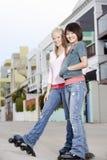 Amis féminins faisant du roller sur la rue Photo libre de droits
