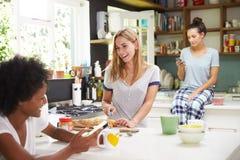 Amis féminins faisant le petit déjeuner tout en vérifiant le téléphone portable Photo libre de droits