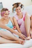 Amis féminins faisant les rouleaux s'usants de cheveu de pedicure Photos libres de droits