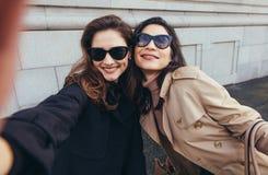 Amis féminins faisant un autoportrait dans la ville Image libre de droits