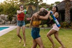 Amis féminins fous ayant l'échange de coups de feu de l'eau Photos stock