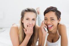 Amis féminins gais à l'aide du téléphone dans le lit Photographie stock libre de droits