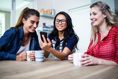 Amis féminins gais à l'aide du téléphone portable par la table à la maison Photo stock