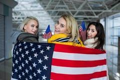 Amis féminins gais étreints dans le drapeau américain Images stock