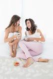 Amis féminins gais avec des tasses de café dans le lit Photographie stock