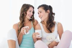 Amis féminins gais avec des tasses de café dans le lit Photos stock