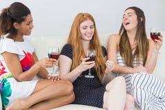 Amis féminins gais avec des verres de vin appréciant une conversation Photos libres de droits