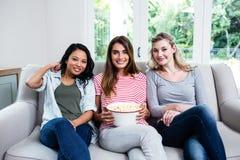 Amis féminins gais avec le maïs éclaté se reposant sur le sofa Photos libres de droits