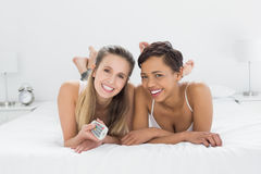 Amis féminins gais avec se situer à télécommande dans le lit Images libres de droits